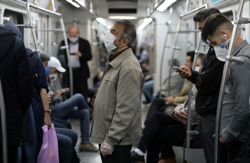 Iranians wear protective face masks, following the outbreak of the coronavirus disease (COVID-19), as they drive with the metro, in Tehran, Iran, May 20, 2020 (photo credit: REUTERS)