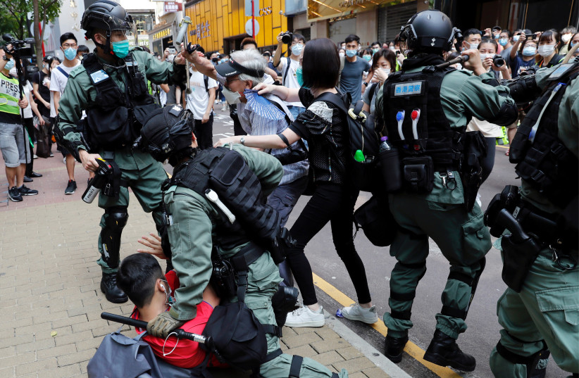 Anti-government demonstrators scuffle with riot police during a lunch time protest as a second reading of a controversial national anthem law takes place in Hong Kong, China May 27, 2020. (photo credit: TYRONE SIU/ REUTERS)