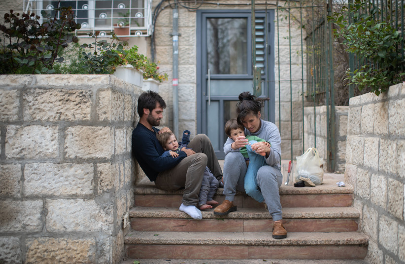 An Israeli family sits on the steps outside their apartment building in Jerusalem, as they stay at home with their children during a nation-wide quarantine, on March 31, 2020.  (photo credit: HADAS PARUSH/FLASH90)