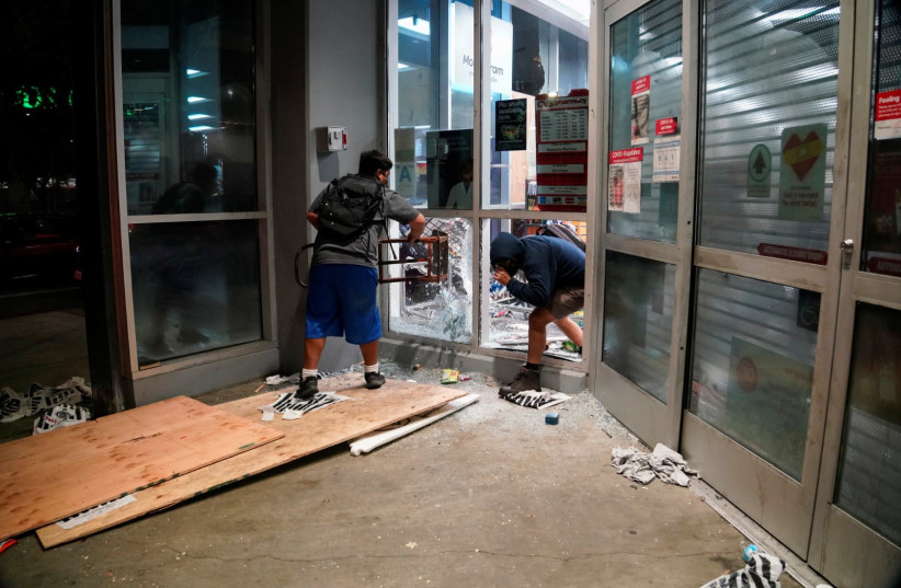 People loot property during nationwide unrest following the death in Minneapolis police custody of George Floyd, in Los Angeles, California, U.S., May 30, 2020. Picture taken May 30, 2020.  (photo credit: REUTERS)
