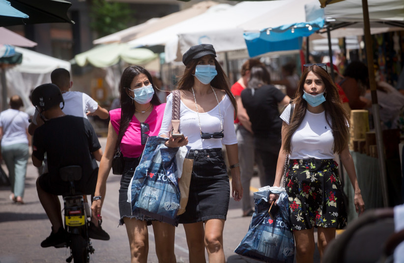 People wear masks as they walk through the  Nahalat Binyamin art market which was reopened, following a closure of several weeks due to the Coronavirus.  June 2, 2020 (photo credit: MIRIAM ALSTER/FLASH90)