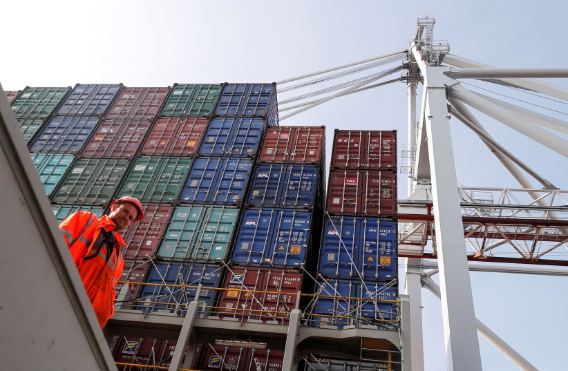 Freight containers are seen on a freight container ship as a worker looks on at DP World, Southampton Docks, in Southampton, Britain, March 27, 2017. (photo credit: REUTERS/EDDIE KEOGH)