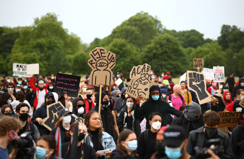 "People wearing face masks hold banners in Hyde Park during a ""Black Lives Matter"" protest following the death of George Floyd who died in police custody in Minneapolis, London, Britain, June 3, 2020. (photo credit: REUTERS / HANNAH MCKAY)"