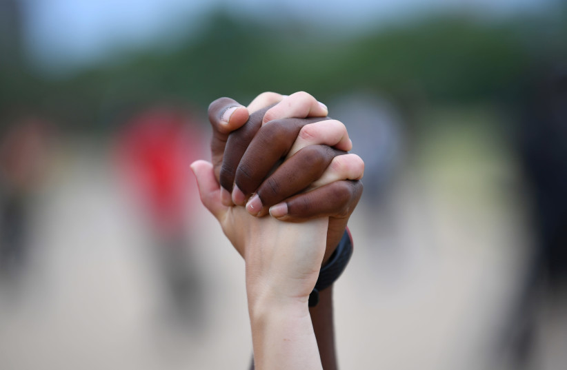 "A man and a woman hold hands aloft in Hyde Park during a ""Black Lives Matter"" protest following the death of George Floyd who died in police custody in Minneapolis, London, Britain, June 3, 2020 (photo credit: REUTERS/DYLAN MARTINEZ)"