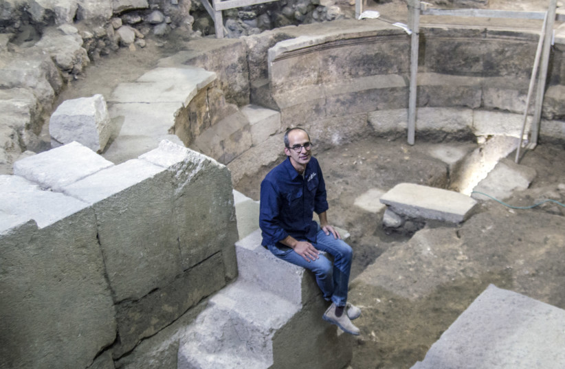 Dr. Joe Uziel of the Israel Antiquities Authority sits on the steps of the theater-shaped building uncovered in the area of Wilson's Arch by the Western Wall.  (photo credit: YANIV BERMAN/IAA)