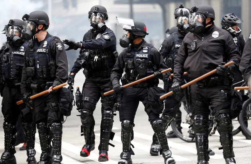 FILE PHOTO: Seattle police form a line after deploying pepper spray and flash-bang devices during a protest against the death in Minneapolis police custody of George Floyd, in Seattle, Washington, U.S. May 31, 2020.  (photo credit: REUTERS/LINDSEY WASSON)