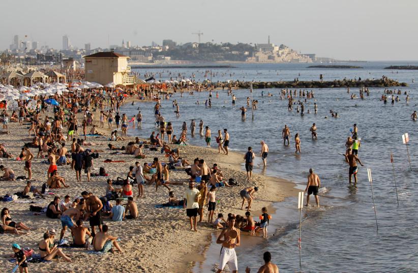 Les baigneurs traînent au bord de la mer Méditerranée à Tel Aviv alors que les restrictions concernant la maladie à coronavirus (COVID-19) se relâchent en Israël le 21 mai 2020 (crédit photo: AMIR COHEN / REUTERS)