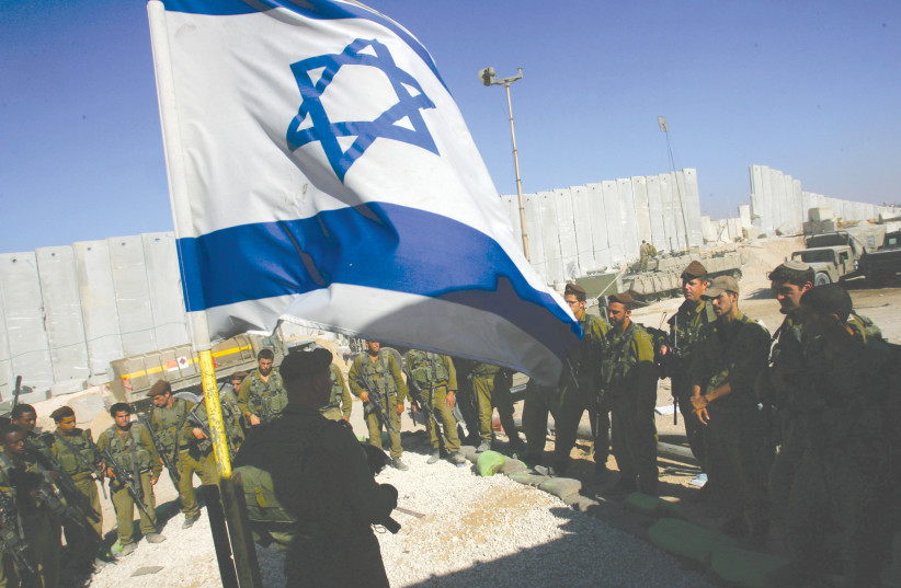 IDF SOLDIERS take part in a flag-lowering ceremony as they prepare to withdraw from Girit outpost, in the southern Gaza Strip, in 2005. (photo credit: DAVID SILVERMAN / REUTERS)