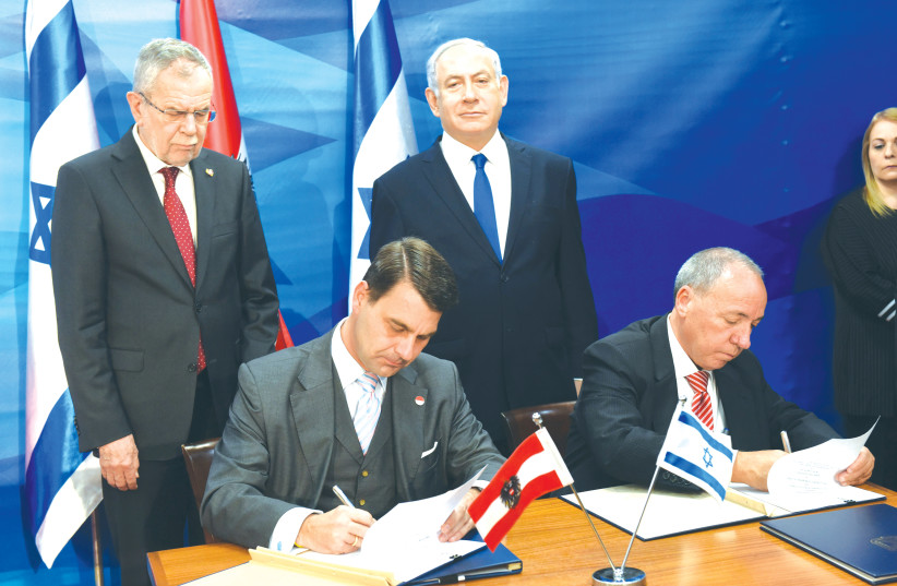 PRIME MINISTER Benjamin Netanyahu and Austrian President Alexander Van der Bellen oversee the signing of agreements between the two countries in Jerusalem last year (photo credit: DEBBIE HILL/REUTERS)