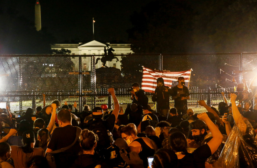 Demonstrators gather behind a fence during a protest against the death in Minneapolis police custody of George Floyd, in Lafayette Park in front of the White House, in Washington, U.S., June 4, 2020 (photo credit: REUTERS/JIM BOURG)