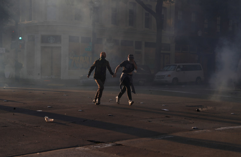 Demonstrators run from tear gas during a rally amid nationwide unrest following the death in Minneapolis police custody of George Floyd, in Oakland, California, U.S., June 1, 2020 (photo credit: STEPHEN LAM / REUTERS)