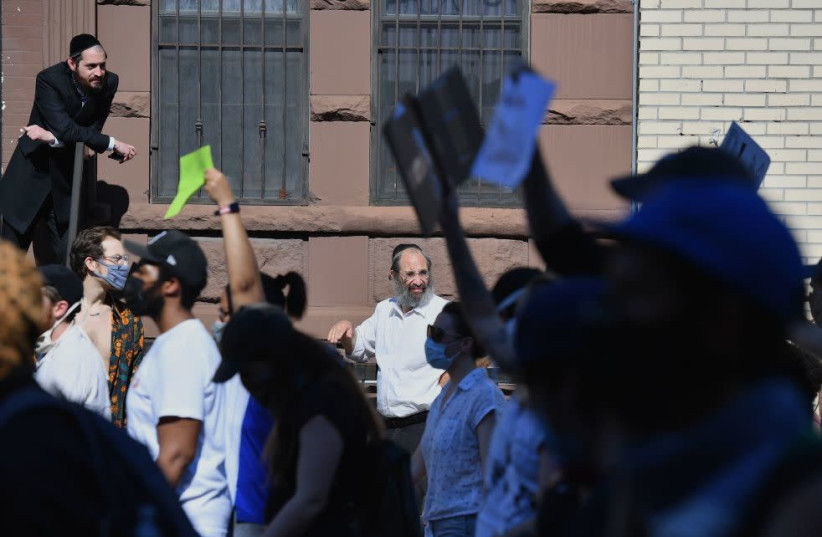 Members of the Orthodox Jewish community watch as protesters walk through the Brooklyn borough on June 3, 2020 (photo credit: ANGELA WEISS/AFP VIA GETTY IMAGES/JTA)