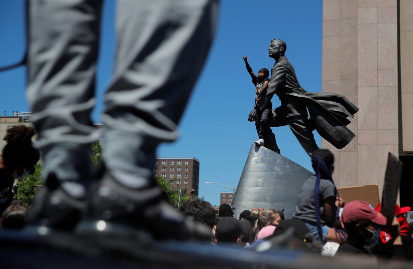 A protester gestures near the statue of Adam Clayton Powell Jr as people rally against the death in Minneapolis police custody of African-American George Floyd, in Manhattan, New York, U.S. (photo credit: REUTERS)