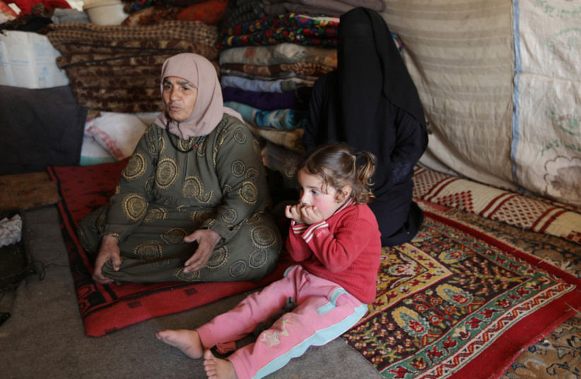 An internally displaced woman, sits with her relatives inside a tent near the town of Afrin, Syria, February 17, 2020 (photo credit: REUTERS/KHALIL ASHAWI/FILE PHOTO)