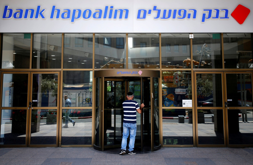 A man enters the main branch of Bank Hapoalim, Israel's biggest bank, in Tel Aviv, Israel July 18, 2016. (photo credit: AMIR COHEN/REUTERS)