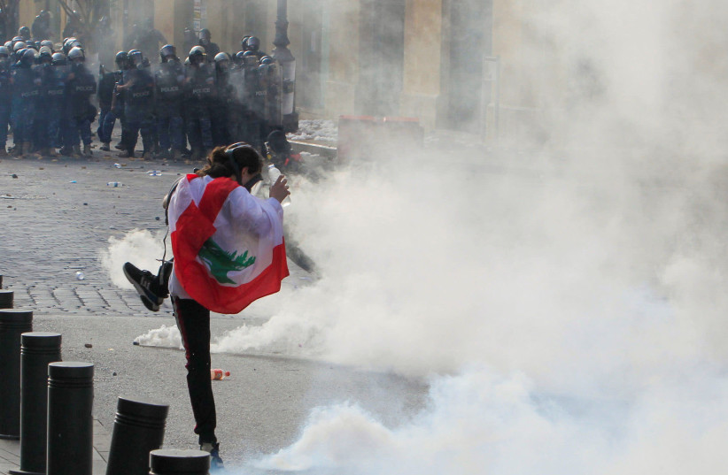 A demonstrator kicks back a tear gas canister during a protest against the government performance and worsening economic conditions, in Beirut, Lebanon June 6, 2020 (photo credit: AZIZ TAHER/REUTERS)