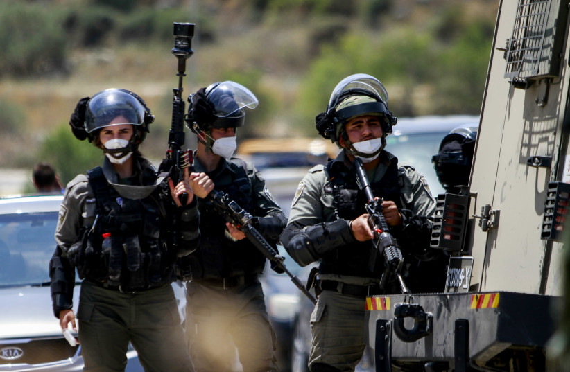 Israeli security forces guard as Palestinians protest against Israel's plan to annex parts of the West Bank, near Tulkarm, in the West Bank on June 5, 2020. (photo credit: NASSER ISHTAYEH/FLASH90)