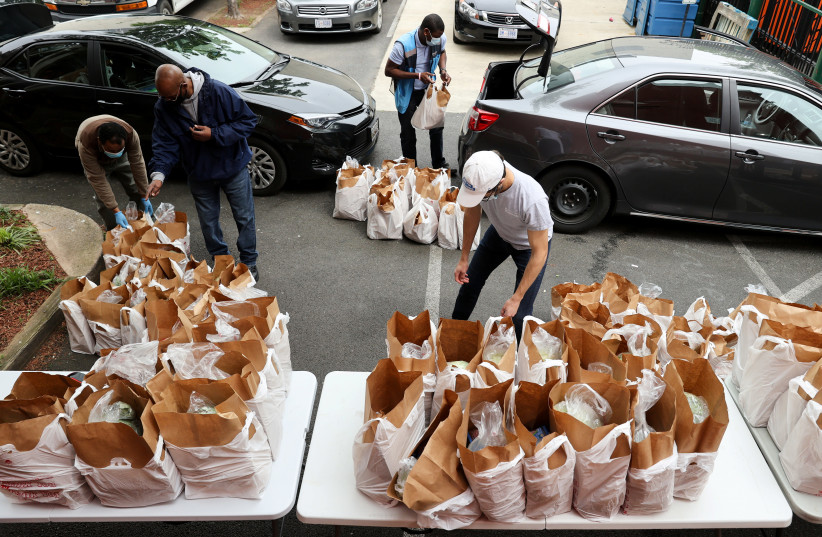 Contract drivers paid by Amazon collect bags of free groceries to deliver from the Bread for the City social services charity during the coronavirus disease (COVID-19) outbreak, in Washington (photo credit: JONATHAN ERNST / REUTERS)