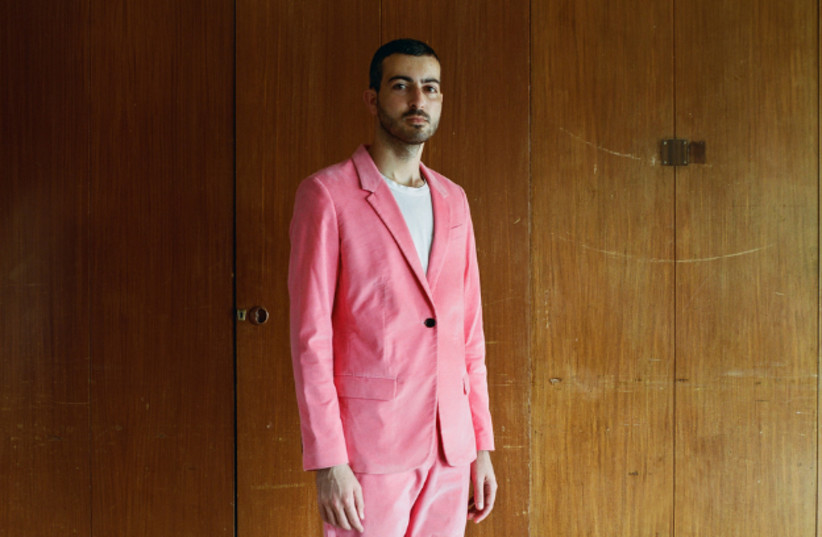 Ofir Lev, from Bezalel Academy's Department of Jewelry and Fashion, wearing a pink women's suit, in his home town, Kibbutz Sde Eliyahu (photo credit: MICHAEL TZUR/BEZALEL ACADEMY'S DEPARTMENT OF PHOTOGRAPHY/VIA VOGUE)