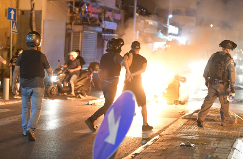 Israel Police officer arrests a protester at a demonstration in Jaffa, June 11, 2020.   (photo credit: ALON HACHMON)