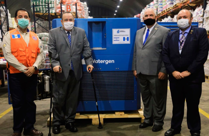 Representatives from Israel and Guatemala stand near a GEN-M atmospheric water generator.  (photo credit: WATERGEN)
