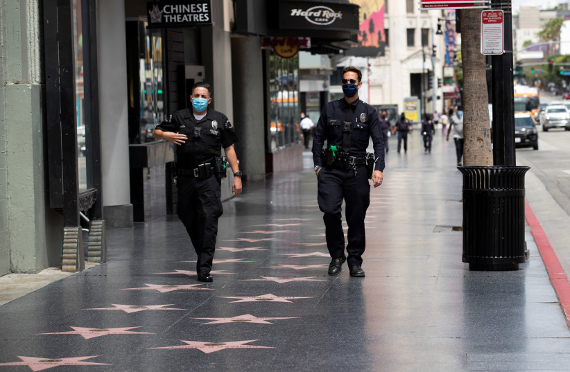 LAPD Officers wear face masks as they patrol Hollywood Blvd during the outbreak of the coronavirus disease (COVID-19), in Los Angeles, California, U.S., May 18, 2020. (photo credit: REUTERS)