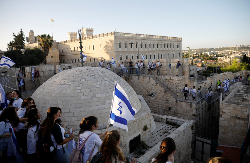 Israelis hold flags and walk on the walls surrounding Jerusalem's Old City while celebrating Jerusalem Day on May 21 (photo credit: RONEN ZVULUN / REUTERS)