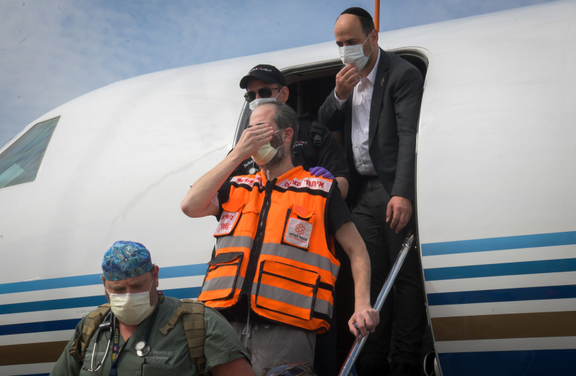United Hatzalah founder and president Eli Beer closes his eyes to recite the 'Shema' as he arrives at Ben-Gurion International Airport on April 21 (photo credit: YEHUDA HAIM/FLASH90)