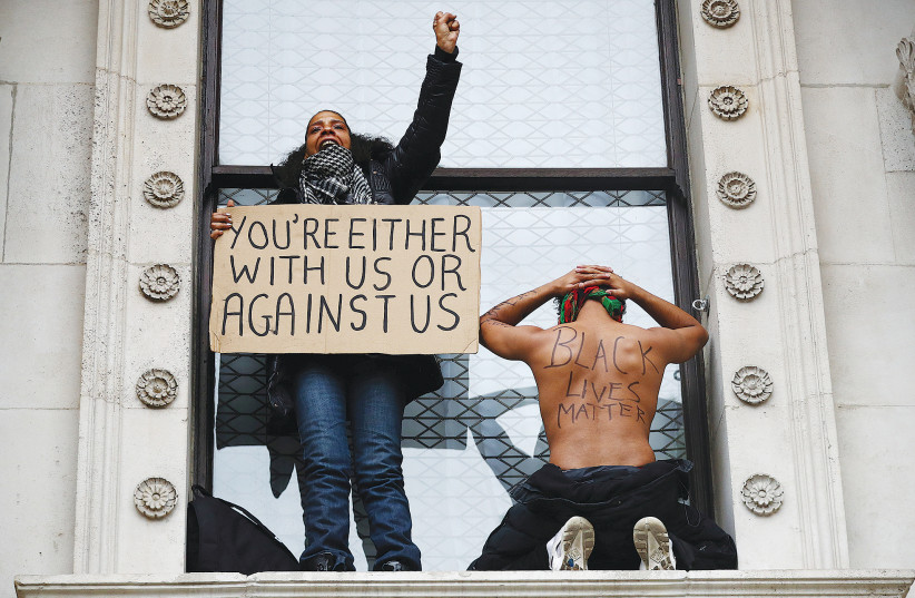 Demonstrators hold up signs during a Black Lives Matter protest in Whitehall, London, on June 7. (photo credit: HANNAH MCKAY/ REUTERS)