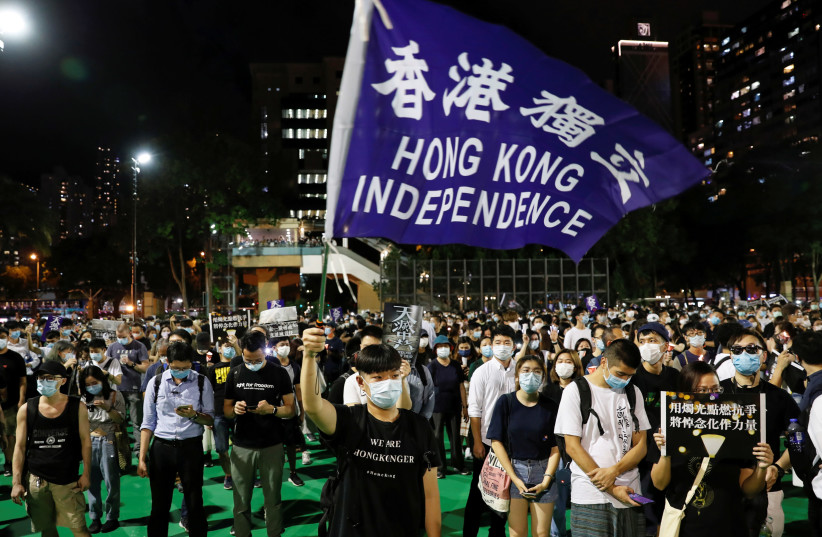 Protesters take part in a candlelight vigil to mark the 31st anniversary of the crackdown of pro-democracy protests at Beijing's Tiananmen Square in 1989. Victoria Park, in, Hong Kong, June 4, 2020. (photo credit: TYRONE SIU/ REUTERS)