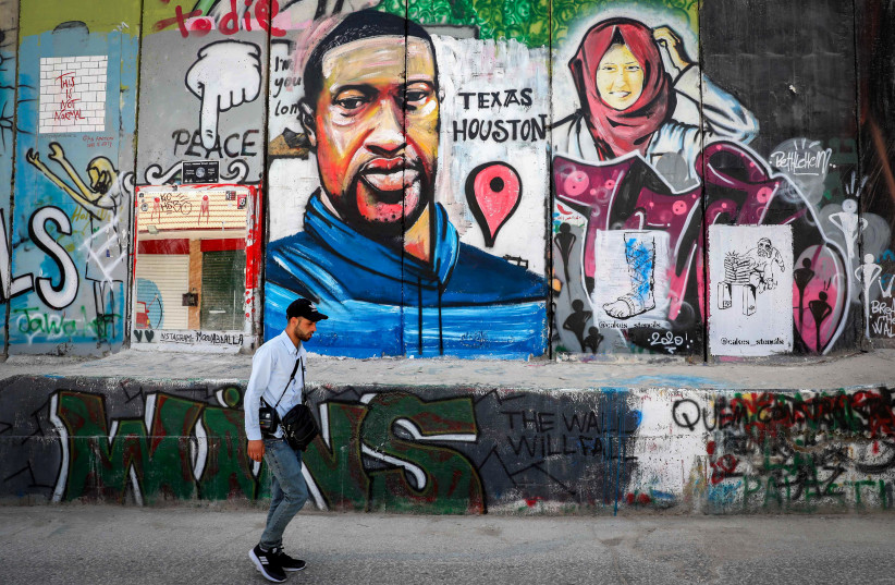 Palestinians walk past graffiti of George Floyd painted on a section of the separation wall in the West Bank city of Bethlehem, on June 8, 2020. (photo credit: WISAM HASHLAMOUN/FLASH90)