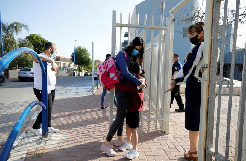A girl hugs her mother before entering her elementary school in Sderot as it reopens following the ease of restrictions preventing the spread of the coronavirus disease. (photo credit: REUTERS/AMIR COHEN)