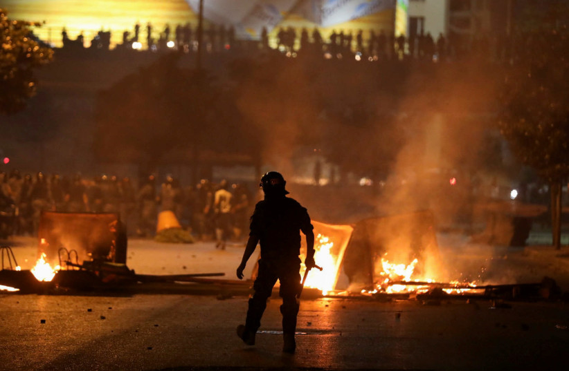 A member of the Lebanese riot police walks near burning fire during a protest, Beirut (photo credit: REUTERS/MOHAMED AZAKIR)