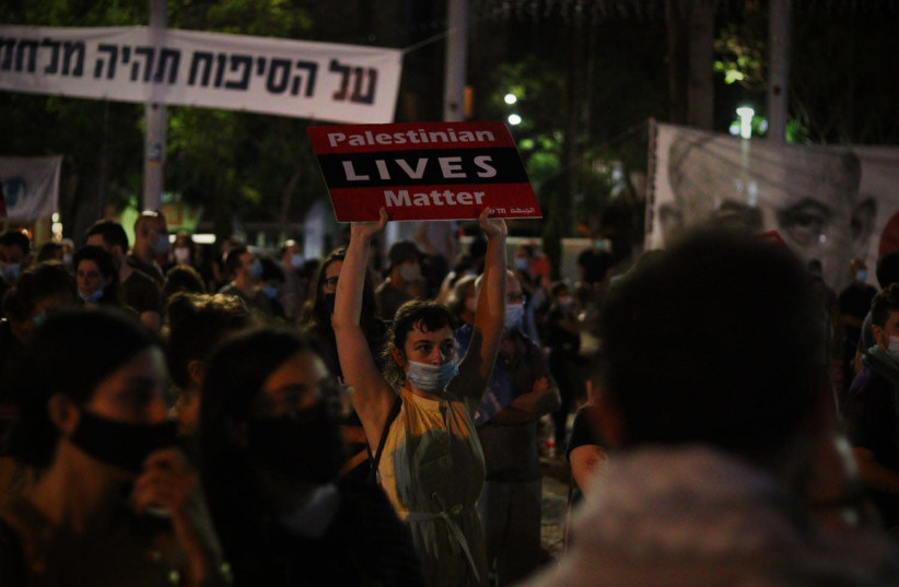 """A protester carrying a """"Palestinian Lives Matter"""" sign at a Tel Aviv protest (photo credit: LEON SVERDLOV)"""