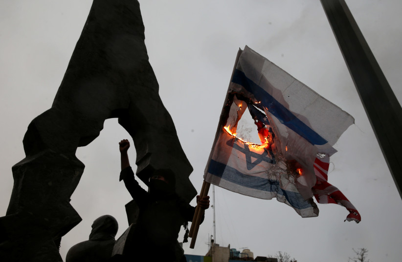 Iranians burn U.S and Israeli flags as they gather to mourn General Qassem Soleimani, head of the elite Quds Force, who was killed in an air strike at Baghdad airport, in Tehran, Iran January 4, 2020 (photo credit: NAZANIN TABATABAEE/WANA VIA REUTERS)