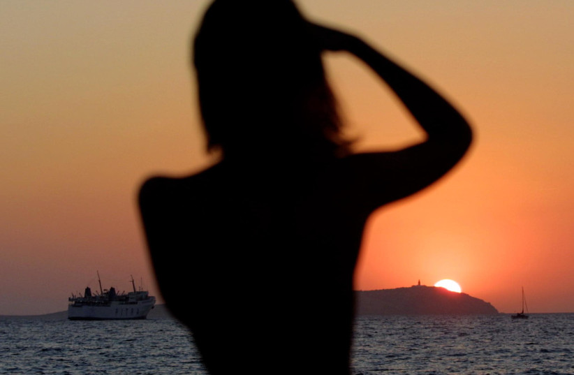 A woman photographs the setting sun on the Spanish island of Ibiza August 29, 2001. Ibiza, one of the most popular tourist attractions in Spain, was hosting the all-night MTV Ibiza 2001 party at Privilege disco which claims to be the largest in the world. (photo credit: REUTERS)