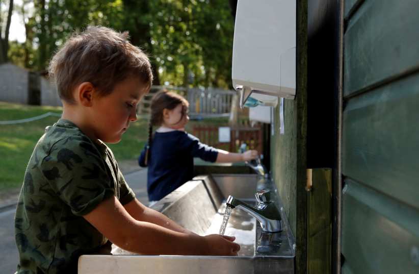 FILE PHOTO: Children are seen washing their hands at Heath Mount School as some schools reopen, following the outbreak of the coronavirus disease (COVID-19), Watton-at-Stone, Britain, June 2, 2020. (photo credit: ANDREW COULDRIDGE/REUTERS)