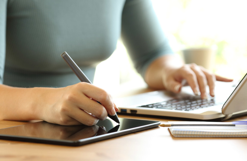 Close up of a woman hands working with a laptop and drawing in a digital tablet on a dek at home or office (Illustrative) (photo credit: INGIMAGE)