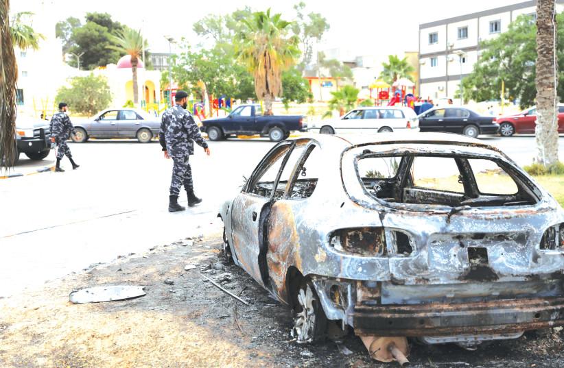 LIBYAN POLICEMEN walk past a destroyed car in Tarhouna, Libya, last week. (photo credit: ISMAIL ZITOUNY/ REUTERS)