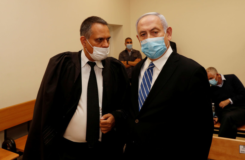 Prime Minister Benjamin Netanyahu, wearing a mask, stands inside the courtroom as his corruption trial opens at the Jerusalem District Court May 24, 2020. (photo credit: REUTERS/RONEN ZEVULUN)