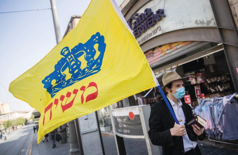 """CHABAD'S 'REDEMPTIVE scenario has a """"tremendous energy"""" which explains """"the amount of sacrifice these people are willing to make""""': A man foists the Chabad flag on Jerusalem's Jaffa Road on April 20. (photo credit: YONATAN SINDEL/FLASH90)"""