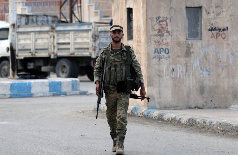 A Turkey-backed Syrian rebel fighter walks next to a wall where is depicted the jailed Kurdistan Workers Party (PKK) leader Abdullah Ocalan, in the border town of Tal Abyad (photo credit: REUTERS)