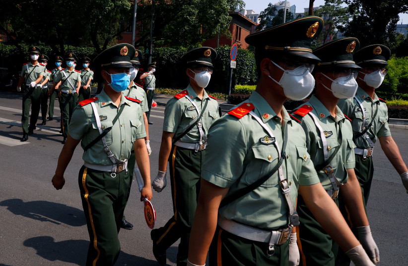 Paramilitary Police officers cross a street in the diplomatic district near a nucleic acid testing site, after a new outbreak of the coronavirus disease (COVID-19) in Beijing, China, June 19, 2020 (photo credit: THOMAS PETER/REUTERS)
