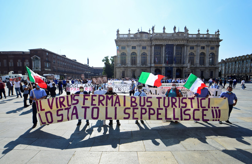 "Owners and drivers of tourist buses hold a banner reading ""The virus stops tourist buses... the state buries them!!!"" Turin, Italy June 3, 2020 (photo credit: MASSIMO PINCA/REUTERS)"