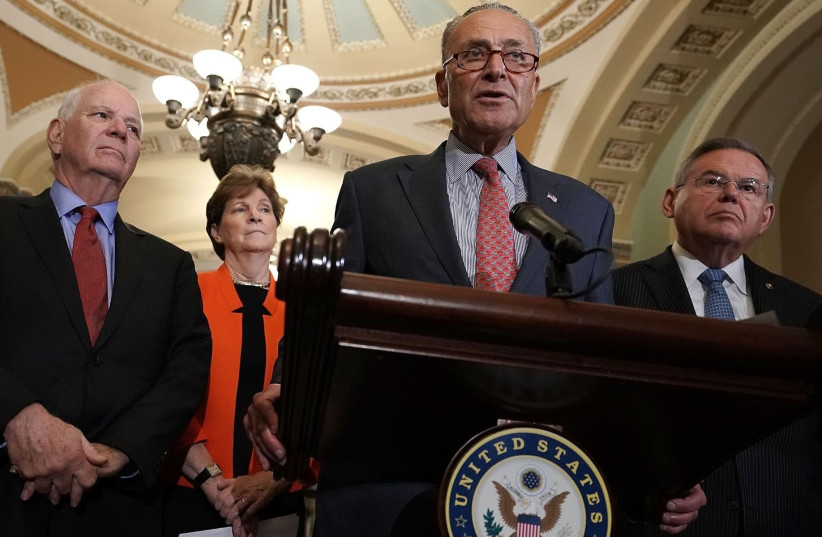 Senate Minority Leader Chuck Schumer, at mic, speaks at a news briefing at the Capitol, July 17, 2018. Left to right in the background are Sens. Ben Cardin, Jeanne Shaheen and Robert Menendez (photo credit: ALEX WONG/GETTY IMAGES/JTA)