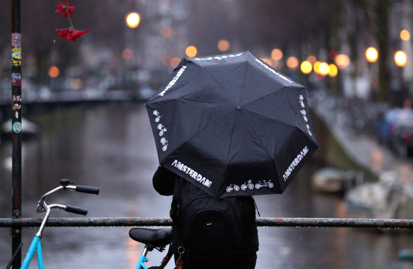 A man holds an umbrella while standing next to a canal in central Amsterdam, Netherlands March 2, 2020 (photo credit: YVES HERMAN/REUTERS)