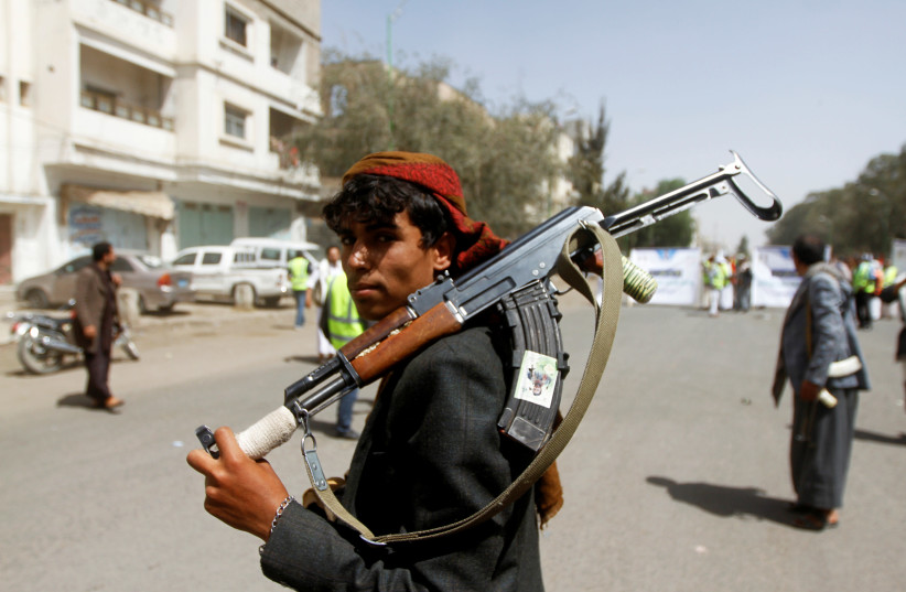 A Houthi supporter looks on as he carries a weapon during a gathering in Sanaa, Yemen April 2, 2020 (photo credit: REUTERS/MOHAMED AL-SAYAGHI)