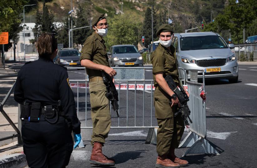 Israeli police and soldiers guard at a roadblock in the Romema neighborhood in Jerusalem (photo credit: NATI SHOHAT/FLASH90)