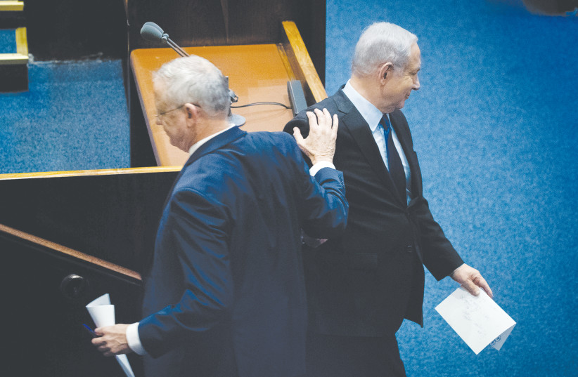 PRIME MINISTER Benjamin Netanyahu and Blue and White Party leader Benny Gantz pass each other in the Knesset last year. (photo credit: YONATAN SINDEL/FLASH90)