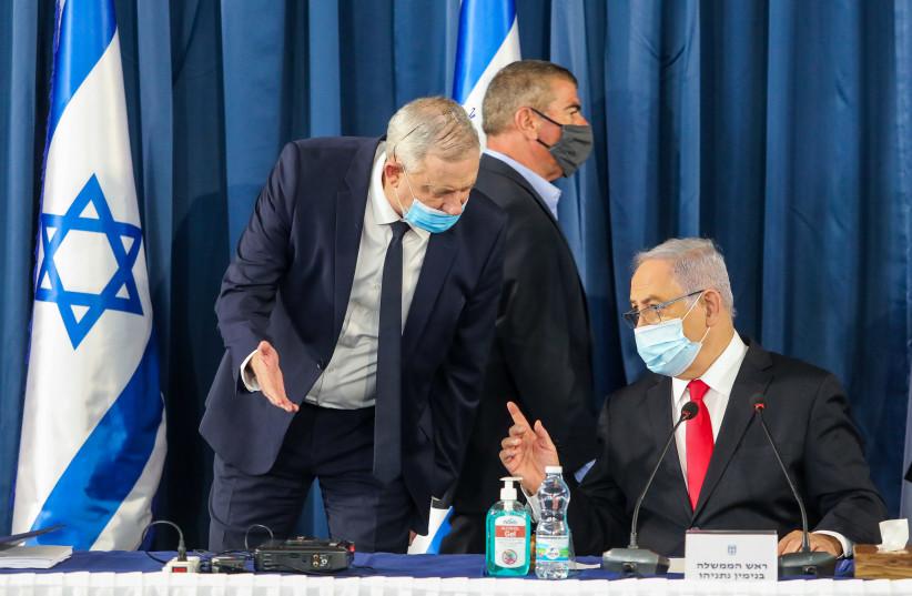 Defense Minister Benny Gantz talks to Prime Minister Benjamin Netanyahu as Foreign Minister Gabi Ashkenazi walks by at a cabinet meeting on June 7 (photo credit: MARC ISRAEL SELLEM)
